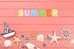 Word Summer with seashells. And decorative ship on wooden table stock photography