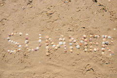 Word Summer shell written on beach sand. Horizontal shot Stock Photography
