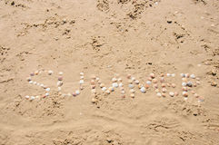 Word Summer shell written on beach sand. Stock Photo