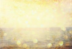 The word summer written on beach sand and gliiter golden lights. Stock Photos