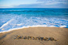 Word summer written in sand on the beach Stock Image