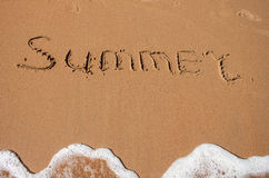 The word summer written in the sand on a beach Stock Photos