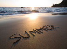 Word summer written in the sand. Of a beach in a sunny sunset Royalty Free Stock Photography