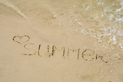 The word summer written on the sand of the beach, washed with water Stock Photo