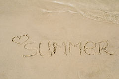 The word summer written on the sand of the beach, washed with water Royalty Free Stock Image