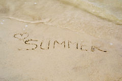 The word summer written on the sand of the beach, washed with water Royalty Free Stock Photo