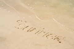 The word summer written on the sand of the beach, washed with water Royalty Free Stock Photography