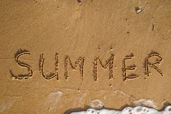 Word summer written on the sand beach. With wave of the sea Royalty Free Stock Photos