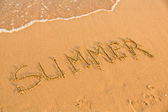 Word summer on the yellow sandy beach Stock Images