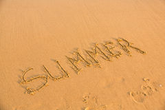 Word summer on the yellow sandy beach Stock Photos