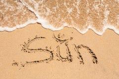 Word Sun écrit dans le sable sur une plage Photographie stock libre de droits