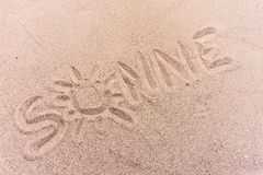 Word sun in german written on the sand of the beach. Word sun Sonne in german written on the sand of the beach stock photo