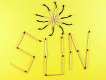 Word Sun made of matchsticks. Isolated on yellow background Royalty Free Stock Photo