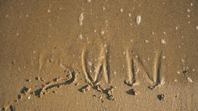 Word `sun` on the sand washed by waves video stock footage