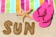 Word - Sun - on a tropical beach. With a striped towel in the colors of the rainbow, pink slip slops and a sea star on sunny golden sand symbolic of travel and Royalty Free Stock Photos