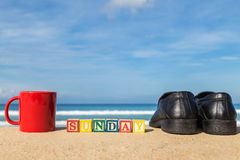 Word SUNDAY in colorful alphabet blocks and coffee cup on tropic Royalty Free Stock Photo
