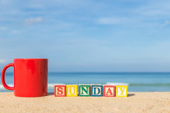 Word SUNDAY in colorful alphabet blocks and coffee cup on tropic Royalty Free Stock Images