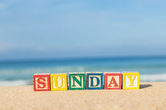 Word SUNDAY in colorful alphabet blocks on tropical beach Stock Images