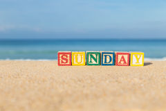 Word SUNDAY in colorful alphabet blocks on tropical beach Royalty Free Stock Image