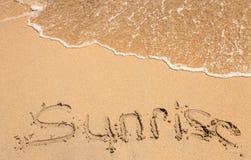 Word sunrise written in the sand Stock Photo