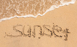 Word sunset written in the sand Royalty Free Stock Photos