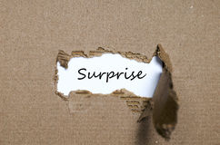 The word surprise appearing behind torn paper Stock Photography