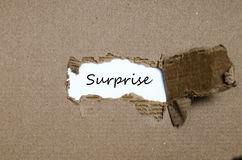 The word surprise appearing behind torn paper Royalty Free Stock Images