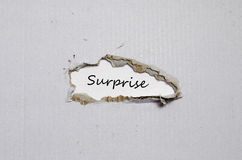 The word surprise appearing behind torn paper Stock Photo