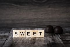 The word sweet is made of bright wood cubes with black letters o. F the English alphabet and 2 chocolates on a dark wooden background Royalty Free Stock Photography