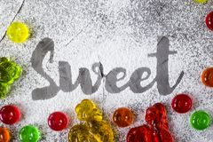 The word sweet is written with powdered sugar. The word sweet is written on a gray concrete background with the help of powdered sugar next to multi-colored Royalty Free Stock Images