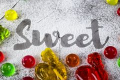 The word sweet is written with powdered sugar. The word sweet is written on a gray concrete background with the help of powdered sugar next to multi-colored Royalty Free Stock Photography