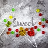 The word sweet is written with powdered sugar. The word sweet is written on a gray concrete background with the help of powdered sugar next to multi-colored Royalty Free Stock Photo