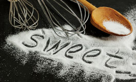 Word sweet written in sugar on a black background. Stock Image