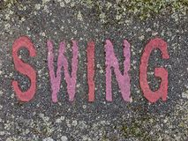 The word SWING on the floor in a kids park. The word SWING stencilled in red and pink letters onto the floor made out of wet pour rubber surface material in a Stock Image