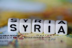 Word SYRIA formed by alphabet blocks on atlas map. Geography Stock Photos