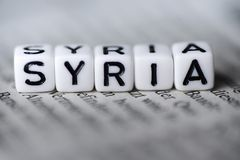 Word SYRIA formed by wood alphabet blocks on newspaper. Closeup Stock Photography