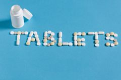 Word Tablets Is Lined With White Pills On A Blue Background Stock Image