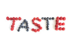 The word Taste written with raspberries and blueberries Royalty Free Stock Image