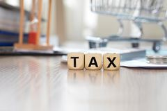 Word TAX composed of wooden letters. Closeup. Word TAX composed of wooden letters. Mini shopping cart,papers, pen in the background. Closeup Royalty Free Stock Image