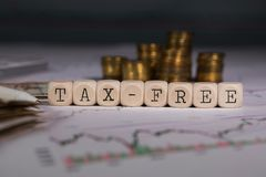 Word TAX-FREE composed of wooden letter. Stacks of coins in the background. Closeup stock photography