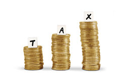Word tax on gold coin stacks Royalty Free Stock Images