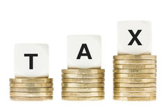 Word TAX on Gold Coin Stacks Isolated with White Background. Taxation, accounting and finance concept. The word TAX on lettered dice on a row of gold coin stacks Stock Photos