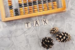Word TAX laid out of handwritten letters on cardboard squares near old wooden abacus and three cones. On gray cracked concrete royalty free stock photo