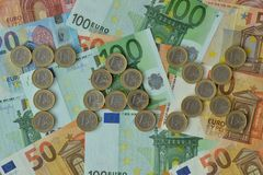 The word Tax written with euro coins on euro banknotes background. Closeup royalty free stock image
