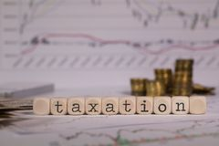 Word TAXATION composed of wooden letter. Stacks of coins in the background. Closeup stock image