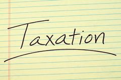 Taxation On A Yellow Legal Pad. The word `Taxation` underlined on a yellow legal pad Stock Photos