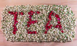 Word tea made of red rose buds in the pile of jasmine flower buds. Flower tea mix. Royalty Free Stock Image