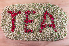 Word tea made of red rose buds in the pile of jasmine flower buds. Flower tea mix. Stock Photography
