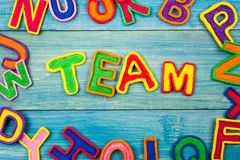 Word TEAM made with plasticine letters on old. Wooden blue board background stock photo