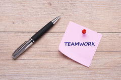 Word teamwork on pink sticky note with red pin Royalty Free Stock Images